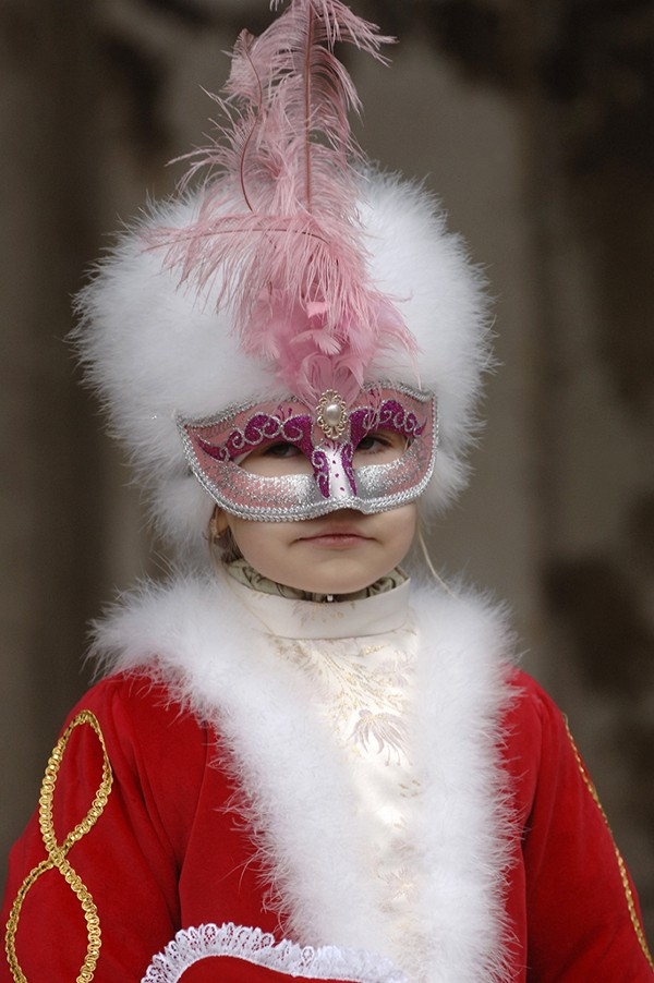 A young girl in a masked outfit photographed at Venice carnival